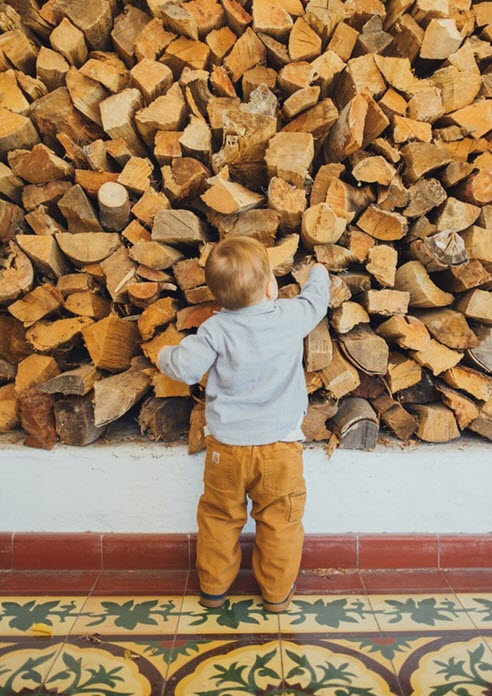 Inquisitive toddler reaching up a wall of chopped wood in a multi cultured atmosphere room